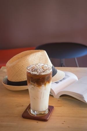 tabel: Ice caramel machiato with book and hat on tabel in coffee shop