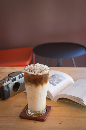 tabel: Ice caramel machiato with book and camera on tabel in coffee shop