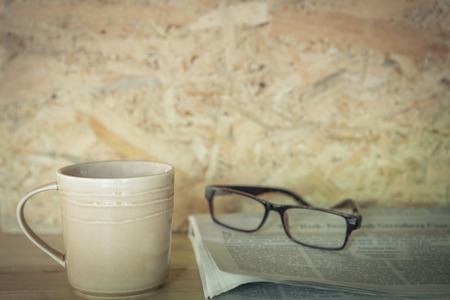 Newspapers and coffee cup, with reading glasses,vintage style image