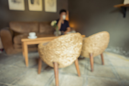 custumer: Coffee shop blur effect with vintage tone , custumer sit on sofa