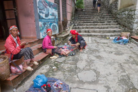 famous women: SAPA, VIETNAM June 14: Red Dao women at a market on June 14, 2015 in Sapa. Sapa is famous for its rugged scenery and its cultural diversity. Red Dao people are one of many colorful tribes. Editorial