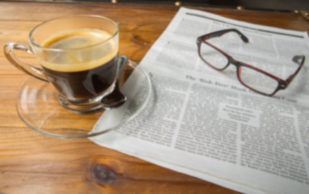 Newspapers and coffee cup, with reading glasses