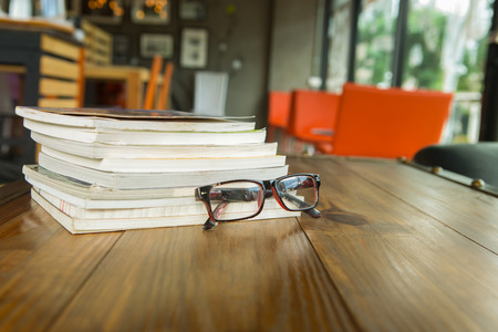 Books with glasses on table, vintage picture style