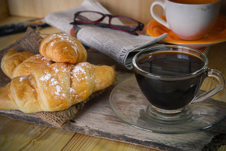 broadsheet newspaper: Cup of coffee with bread at reading time with newspaper