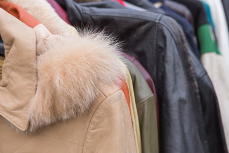 used clothes: Closeup of some used leather clothes hanging on a rack in a flea market