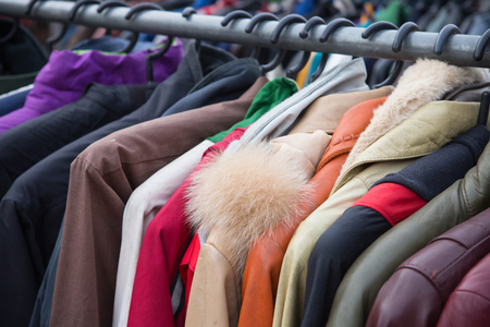 used clothes: Selective focus some used leather clothes hanging on a rack in market