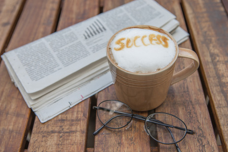 tabel: Cup of coffee with wording  success  and glasses on  Business newspaper Stock Photo