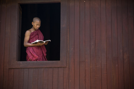 devout: BAGAN, MYANMAR Dec 13: a young novice stydying at window of chamber temple on Dec13,2015 in Bagan, Myanmar. Boys at 8-20 years old have to enter the Buddhist Order as a novice. Editorial