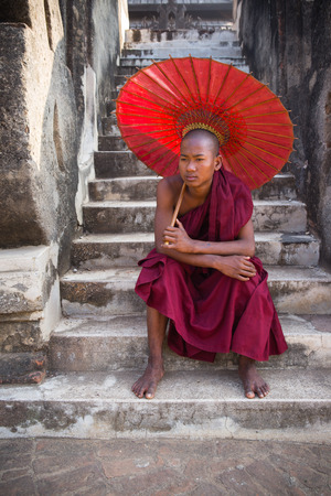 sit down: BAGAN, MYANMAR - December 13, : Unidentified young Buddhism novices sit down on stairs archway at temple on December 13, 2015 in Bagan, Myanmar. Editorial