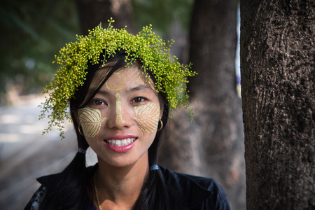 thanaka: MANDALAY MYANMAR- Dec 9: Young woman of Burmese with thanaka and flower above head ,She is happiness for sale souvenir on Dec 28, 2015.Mandalay,Myanmar Editorial