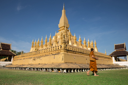 vientiane: Wat Phra That Luang (Golden Pagoda ) with monk moving in  Vientiane ?The land mark of Vientiane capital Laos Stock Photo