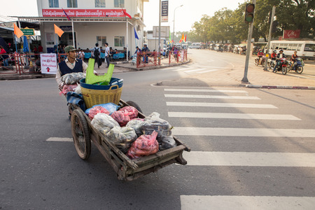 coolie hat: Vientiane,Laos- Jan 17 ;A vendors of Lao pushing wood cart on main road at Morning Market Vientiane on January 17,2016 . Vientiane , Laos . Editorial