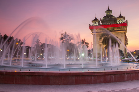 forground: Patuxay monument with water fountain forground at twilight ,the landmark of city Vientiane Laos Stock Photo