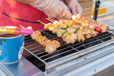 broil: Selective focus BBQ chicken kebabs on grill with flames