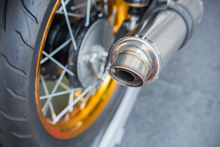 chromed: Selective focus big chromed exhaust on motorcycle, photographed from behind
