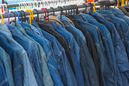 shoulder buttons: Selective focus jeans of shirt on rack Stock Photo