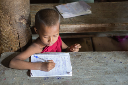 MANDALAY,MYANMAR-Dec 9 :Young Novice Monk studying Pali Buddhist book at Shwenandaw Monastery or Golden Palace Monastery on December 9,2015 in Mandalay city, Middle of Myanmar Editoriali