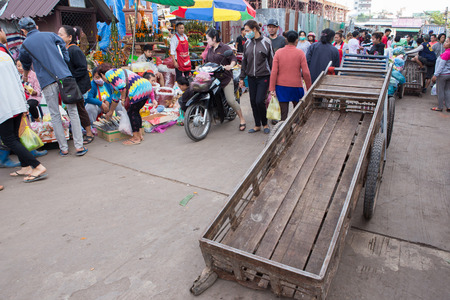 coolie hat: Vientiane , Laos - Jan 17 ; A cart man in Morning Market Vientiane pushing a cart carry some food of costumer  on January 17,2016 .Service in market for heavy weight goods, Vientiane Laos .