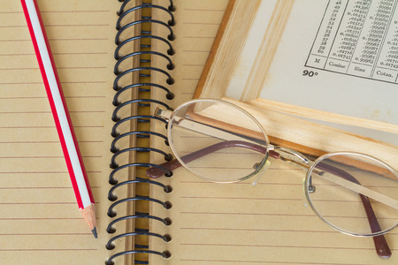 derivative: Glasses with pencil on lecture book and math book . vintage tone color