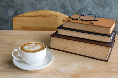 turn table: Cup of latte coffee with vintage book and glasses turn over on rustic table