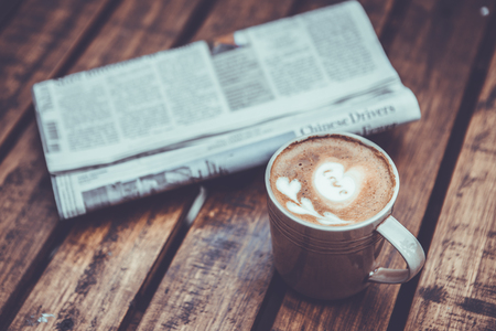 A newspaper and a cup of coffee on a wooden table
