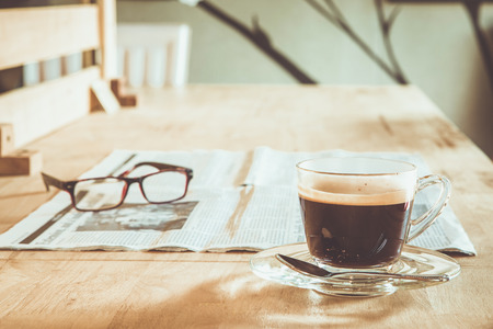Cup of coffee with newspaper and glasses on table Stock Photo