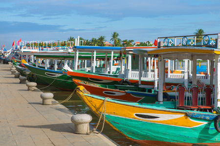 Wooden boats on the Thu Bon River in Hoi An Ancient Town (Hoian), Vietnam. Yellow old houses on waterfront. Stock Photo