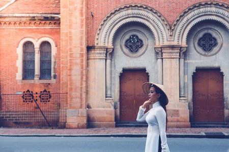 HOCHIMINH CITY, VIETNAM, NOVEMBER 04 : unidentified Vietnamese girls wearing white Ao dai on the street on November 04, 2016. Ao dai is famous traditional Custume for women in Vietnam.
