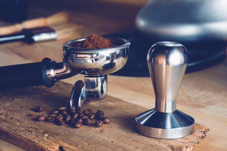 Freshly ground coffee beans in a metal filter on a wooden with coffee bean