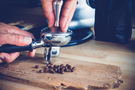 Man is using a tamper to press freshly ground morning coffee into a coffee tablet Archivio Fotografico