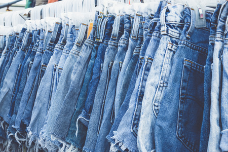 slacks: Selective focus row of hanged blue jeans in a shop