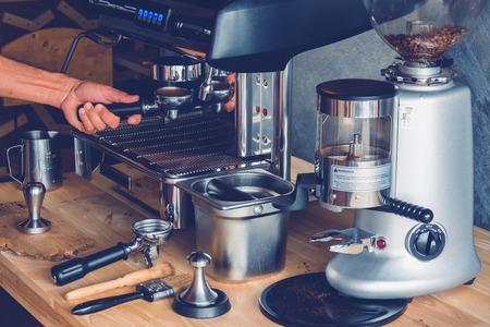 Hand of Barista put a portafilter to espresso machine for brewing coffee
