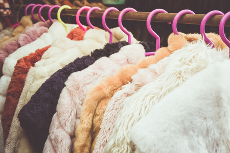 Closeup of some used leather clothes hanging on a rack in a  market