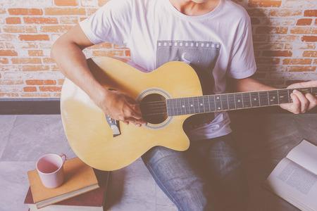 music lyrics: Un hombre que toca la guitarra en el suelo con el libro Foto de archivo