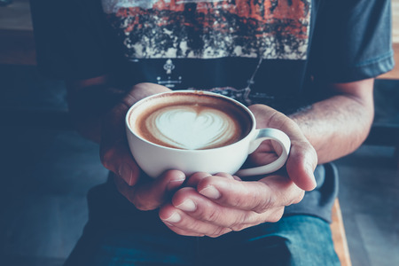 to get warm: Morning coffee, hands holding cup of hot coffee latte cappuccino with heart shaped foam