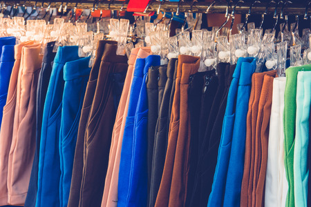 trouser: Colorful man and womans short pants on hangers in a retail shop