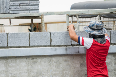 putty knives: Worker installing red brick for construction site