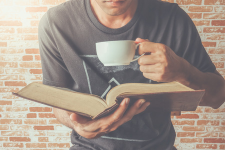 A man read old book on tea or coffee time