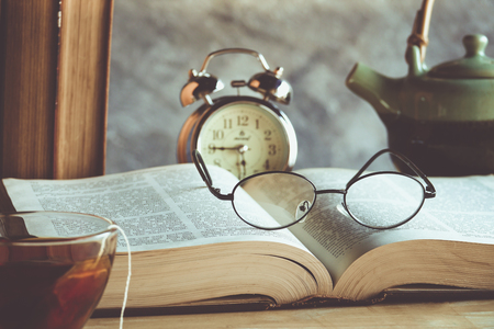 law school: Closeup of reading glasses on the book with tea cup and clock