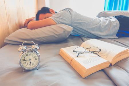 Een man die op bed na gelezen boek slaapt