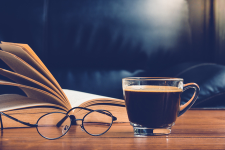 tarde de cafe: Cup of coffee with glasses and book on table in afternoon time