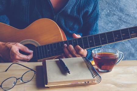 若い男が紅茶のカップをテーブルの上のギターと歌を作曲 写真素材