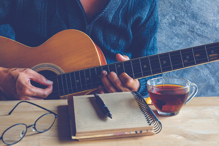 Young man composing the song with guitar on table with tea cup