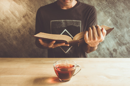 A cup of tea with a man reading book on table