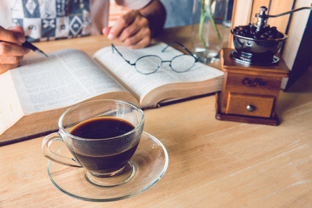 A man holding a pen and holding cup of coffee with old book on table Stock Photo