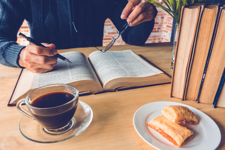 A man holding a pen with a cup of coffee in front of old book on table