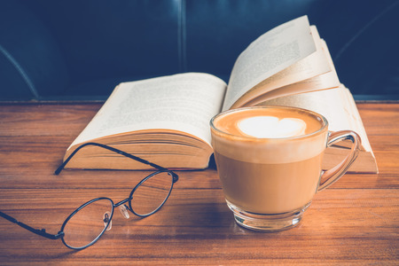 cup of latte or cappuccino coffee with glasses and  a book in coffee shop
