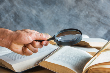 magnifying glass in hand and book on the table Archivio Fotografico