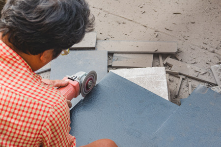 cut off saw: Worker cutting and grinding concrete or metal using a cut-off saw
