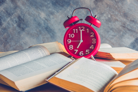 Red alarm clock on stack old books Stock Photo